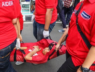Seorang korban tengah dibawa saat simulasi Peringatan P3K Sedunia di CFD Jalan MH Thamrin, Jakarta, Minggu (25/9). Aksi bersama Hansaplast mengajak masyarakat siapkan perlengkapan P3K sejak dini. (Liputan6.com/Fery Pradolo)