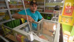 Hendri (37) membersihkan toko jamu aduk miliknya di kawasan Pamulang, Tangerang Selatan, Banten, Senin (28/9/2020). Menurutnya penjualan jamu aduk pada masa musim pandemi Covid 19 satu bulan ini penjualan meningkat hingga 200 persen dibandingkan bulan sebelumnya. (merdeka.com/Dwi Narwoko)