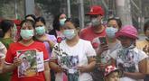 Warga membawa bunga mawar sebagai penghormatan kepada seorang guru yang tewas dalam protes kudeta militer di Yangon, Myanmar, Senin (1/3/2021).  Seorang guru perempuan tewas setelah polisi melemparkan granat setrum untuk membubarkan aksi protes yang digelar para guru di Yangon. (AP Photo)