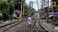 Seorang wanita melintasi rel kereta di kawasan pemukiman padat Pejompongan di tengah pandemi COVID-19, Jakarta, Kamis (28/1/2020). Sensus Penduduk 2020 (SP2020) mencatat penduduk DKI Jakarta pada bulan September 2020 sebanyak 10,56 juta  jiwa. (Liputan6.com/Johan Tallo)