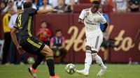 Striker Real Madrid Vinicius Junior mengumpan bola dari kawalan bek Juventus Giorgio Chiellini selama babak kedua pertandingan International Champions Cup (ICC) di Landover, Md (4/8). Madrid menang telak 3-1 atas Juventus. (AP Photo/Nick Wass)