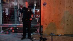 Seorang petugas polisi berdiri di luar sebuah toko yang rusak di lingkungan Chelsea di New York (1/6/2020). George Floyd meninggal pada 25 Mei setelah ia dijepit di leher oleh seorang petugas kepolisian Minneapolis. (AP Photo/Craig Ruttle)