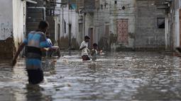 Warga melintasi jalan banjir setelah hujan deras di Karachi, Pakistan, Minggu, (26/7/2020). Sebagian warga memilih untuk bertahan meski rumah mereka terendam banjir. (AP Photo/Fareed Khan)
