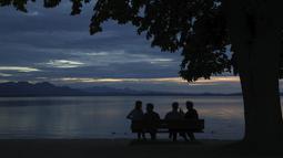 Orang-orang menikmati matahari terbenam di danau Chiemsee di Chieming, Jerman, Selasa, (25/8/2020). Chiemsee terbagi menjadi dua bagian, yaitu bagian timur laut yang lebih besar yang disebut Weitsee serta bagian Inselsee yang terletak di barat daya. (AP Photo / Matthias Schrader)