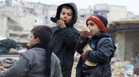 Dua orang anak makan roti sambil menunggu untuk dievakuasi dari sektor yang dikuasai pemberontak, Aleppo, Suriah (9/12). (REUTERS / Abdalrhman Ismail)