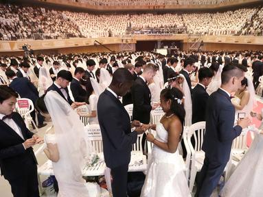 Pasangan pengantin bertukar cincin dalam pernikahan massal di Cheong Shim Peace World Center, Gapyeong, Korea Selatan, Senin (27/8). Acara ini diikuti sekitar 3.800 pasangan pengantin. (AP Photo/Ahn Young-joon)