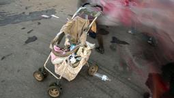 Imigran yang sebagian besar penduduk Honduras melewati kereta bayi yang rusak dalam perjalanan menuju AS di Pijijiapan, Meksiko, 26 Oktober 2018. Kereta dorong bayi telah menjadi barang mewah bagi para imigran dalam perjalanan mereka (Guillermo Arias/AFP)