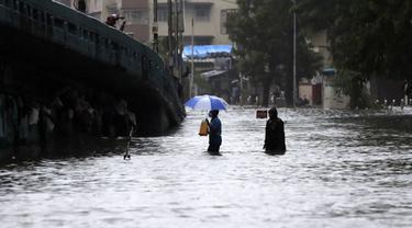 Orang-orang menyeberang jalan melintasi banjir saat hujan lebat di Mumbai, India, Rabu, (5/8/2020). Musim hujan India berlangsung dari Juni hingga September. (AP Photo/Rajanish Kakade)