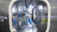 Seorang teknisi laboratorium yang mengenakan alat pelindung diri (APD) bekerja pada sampel yang akan diuji untuk virus corona Covid-19 di laboratorium Mata Api, fasilitas pengujian Covid-19, di Wuhan di provinsi Hubei tengah China (5/8/2021). (AFP/STR)