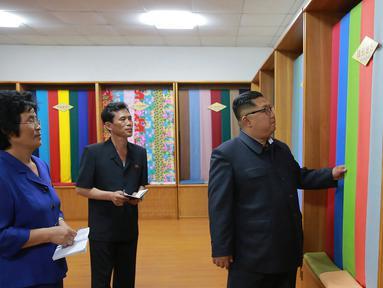 Pemimpin Korea Utara, Kim Jong-un melihat bahan saat mengunjungi Sinuiju Chemical Fiber Mill di Sinuiju, Korea Utara (2/7). (AFP Photo/KCNA Via KNS)