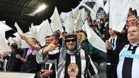 Penggemar Newcastle United mengibarkan bendera hitam putih dan spanduk untuk merayakan pengambilalihan klub oleh konsorsium yang dipimpin Pangeran Arab Saudi selama pertandingan antara Newcastle United dan Tottenham Hotspur di St James' Park, Minggu (17/10/2021). (AFP/Paul Ellis)
