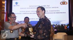 Kapolri Jenderal Polisi Tito Karnavian dan Kepala BKPM Thomas Lembong bertukar cindera mata, Jakarta, Senin (19/9). Acara ini merupakan wujud pedoman kerja tentang koordinasi perlindungan dan keamanan bagi dunia usaha. (Liputan6.com/Immanuel Antonius)