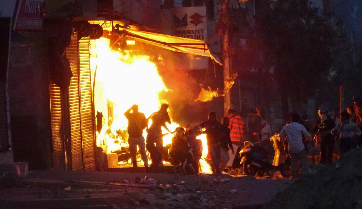 Massa membakar sebuah toko saat bentrok antara pendukung dan penentang Undang-Undang Kewarganegaraan baru di New Delhi, India, Selasa (25/2/2020). Bentrokan menewaskan 15 orang dan melukai ratusan lainnya. (AP Photo)