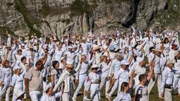 Anggota gerakan keagamaan internasional White Brotherhood menari di puncak Gunung Rila, Bulgaria, Senin (19/8/2019). Tarian tersebut ditampilkan dalam lingkaran konsentris yang mereka yakini dapat menghubungkannya dengan ritme kosmik dan melawan kesedihan. (NIKOLAY DOYCHINOV/AFP)