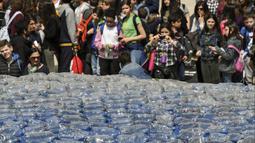 Anak-anak mengambil gambar patung paus raksasa, Plasticus yang dipajang di depan Auditorium Parco della Musica, Roma, Italia, Senin (16/4). Plasticus dibuat untuk meningkatkan kesadaran tentang masalah pencemaran plastik di laut. (Andreas SOLARO/AFP)
