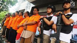 Polisi mengawal tersangka kasus mafia tanah di wilayah Jakarta dan Bekasi, Polda Metro Jaya, Jakarta, Rabu (5/9). Dalam kasus ini polisi berhasil mengamankan 19 tersangka. (Liputan6.com/JohanTallo)