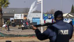 Orang-orang melempari polisi dengan batu ketika mereka mencoba menjarah di Pusat Perbelanjaan Letsoho di Katlehong, sebelah timur Johannesburg, Senin (12/7/2021). Kerusuhan dan penjarahan yang dipicu penahanan mantan Presiden Afrika Selatan Jacob Zuma. (AP/Themba Hadebe)