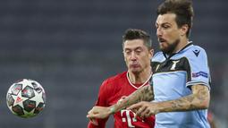 Penyerang Bayern Munchen, Robert Lewandowski dan bek Lazio, Francesco Acerbi berebut bola pada leg kedua babak 16 besar Liga Champions di Allianz Arena, Kamis dinihari WIB (18/3/2021). Munchen menang 2-1 atas tamunya Lazio dan maju ke perempatfinal dengan agregat 6-2. (AP Photo/Matthias Schrader)