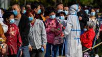 Petugas medis mengukur suhu warga saat mereka antre untuk tes COVID-19 di dekat daerah perumahan di Qingdao, China, Senin (12/10/2020). Lebih dari 9 juta orang yang tinggal di kota Qingdao, menjalani tes virus Corona (COVID-19) secara massal setelah muncul kasus baru. (STR/AFP)