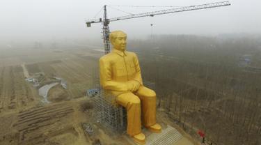 Sebuah Crane saat beroperasi di sebelah patung Presiden pertama Cina, Mao Zedong saat proses penyelesaian pembangunannya di ladang Desa Tongxu, Henan, Cina (4/1). Patung ini memiliki tinggi 36,6 meter dan dilapisi cat emas. (Reuters/Stringer)