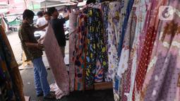 Calon pembeli memilih kain di Pasar Cipadu, Tangerang, Selasa (2/3/2021). Pandemi Covid-19 membuat industri tekstil dan pakaian jadi mengalami pertumbuhan negatif 8, 8% sepanjang 2020, bahkan pandemi membuat tenaga kerja di sektor industri tekstil berkurang hingga 13%. (Liputan6.com/Angga Yuniar)