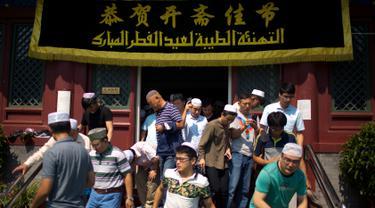Umat muslim Cina meninggalkan masjid Niujie, Beijing, seusai pelaksanaan salat Idul Fitri, 26 Juni 2017. Masjid Niujie merupakan Masjid bersejarah di Kota Beijing dan mnjadi tempat ibadah masyarakat muslim. (AP Photo/Mark Schiefelbein)
