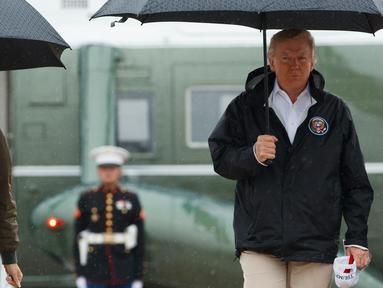 Presiden AS, Donald Trump dan Ibu Negara Melania Trump berjalan menuju pesawat kepresidenan di Pangkalan AU Andrews, Maryland, Selasa (29/8). Trump akan melakukan perjalanan ke Texas guna meninjau lokasi pasca Badai Harvey. (AP Photo/Evan Vucci)