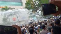 Polisi menyemprotkan watercanon di tengah bentrok mahasiswa di depan gedung DPRD Sumsel (Liputan6.com / Nefri Inge)