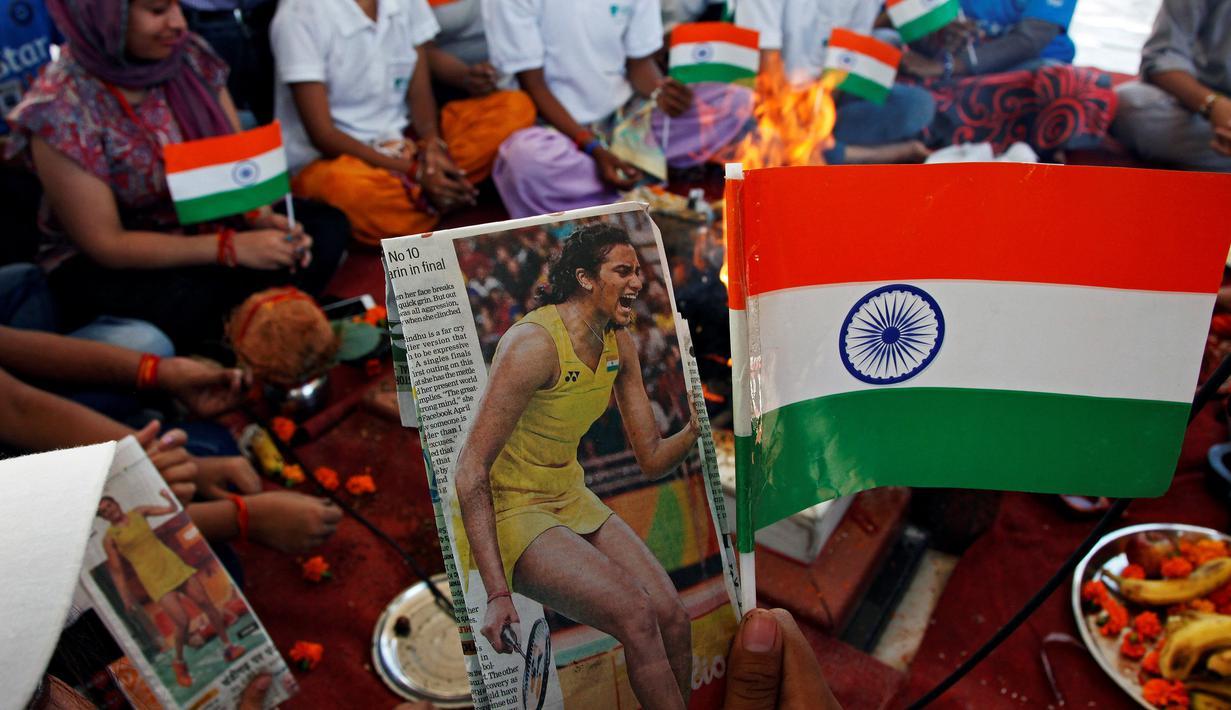 Warga saat melakukan ritual doa untuk atlet bulu tangkis mereka, P.V. Sindhu yang sedang mengikuti Olimpiade 2016 untuk mendapatkan medali emas di Chandigarh , India , 19 Agustus 2016. (REUTERS / Ajay Verma)