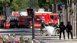 Petugas penyelamat menutupi jasad seorang pria usai menabrakkan mobilnya ke van polisi di jalan Champs Elysees, Paris, Senin (19/6). Belum diketahui pelaku tewas karena hantaman mobil atau tindakan dari polisi. (AP Photo/Thibault Camus)