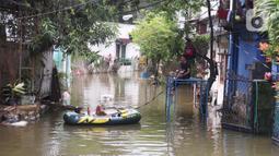 Seorang warga beristirahat di perahu karet saat banjir melanda perumahan Periuk Damai, Tangerang, Banten, Selasa (22/2/2021). Ratusan rumah masih terendam banjir sampai menyentuh ke atap rumahnya. (Liputan6.com/Angga Yuniar)