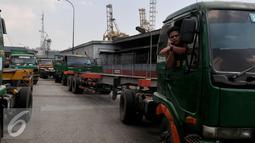Seorang supir berada di truknya saat tertahan di depan gerbang pintu masuk JICT, Tanjung Priok, Jakarta, Selasa (28/7/2015). Kegiatan distribusi barang dan peti kemas dari dan ke pelabuhan lumpuh akibat aksi mogok pekerja JICT. (Liputan6.com/JohanTallo)