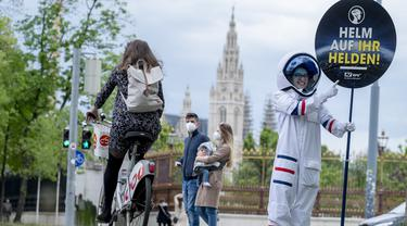 Seorang pesepeda diperlihatkan peringatan untuk mengenakan helm oleh siswa berkostum astronaut, di Ring Street, Wina, Austria, Rabu (5/5/2021). Delapan siswa Wina berpartisipasi dalam acara tersebut untuk mengingatkan pengendara sepeda mengenakan helm demi keamanan mereka. (JOE KLAMAR/AFP)