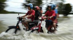 Pengendara motor melintasi jalan yang terkena banjir di kawasan Jal Besar, Malaysia, Kamis (5/1). Sekitar 23 ribu orang terpaksa mengungsi karena banjir yang disebabkan hujan muson ini. (AFP PHOTO / MOHD RASFAN)