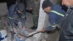 Para pekerja membersihkan puing ledakan bom bunuh diri di dalam kantor polisi di kawasan Midan, Damaskus, Suriah, 16 Desember 2016. Diketahui gadis cilik pelaku bom tersebut tewas dan seorang polisi terluka. (SANA/Handout via Reuters)