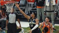 Forward Milwaukee Bucks Giannis Antetokounmpo mencoba memasukkan bola ke keranjang melewati dua pemain Phoenix Suns Devin Booker dan Deandre Ayton pada Game 6 Final NBA di Milwaukee, Rabu, 21 Juli 2021. (AP Photo/Paul Sansya)