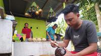 Eman Gani sedang membuat kerajinan tempurung kelapa di rumahnya di Kelurahan Bulotadaa Timur, Kecamatan Sipatana, Kota Gorontalo. (Liputan6.com/ Arfandi Ibrahim)