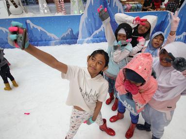 Anak-anak berselfie saat bermain sajlu di Snow Village di salah satu pusat perbelanjaan di kawasan Tangsel, Senin (17/12). Jelang Natal dan Tahun Baru sejumlah pusat perbelanjaan menyajikan kegiatan untuk menarik pengunjung. (Merdeka.com/Arie Basuki)