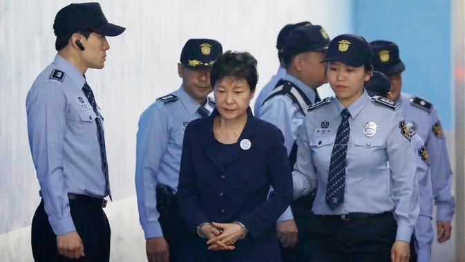 Mantan Presiden Korsel Park Geun-hye dengan tangan diborgol tiba di Pengadilan Distrik Pusat Seoul, Korea Selatan (23/5). Park Geun-hye menjalani sidang perdana atas serangkaian tuduhan korupsi yang dialamatkan kepadanya. (Kim Hong-ji/Pool Photo via AP)