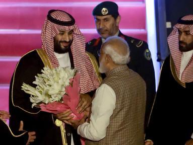 PM India, Narendra Modi memberikan bunga saat menyambut Putra Mahkota Arab Saudi Pangeran Mohammed bin Salman di bandara New Delhi, Selasa (19/2). Modi memutuskan  melanggar protokoler untuk secara pribadi menyambut Putra Mahkota Saudi. (AP/Manish Swarup)