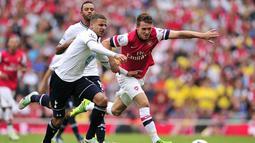Gelandang Arsenal Welsh Aaron Ramsey (kanan) duel dengan bek Tottenham Hotspur Kyle Walker (kiri) pada pertandingan sepak bola Liga Utama Inggris antara Arsenal dan Tottenham Hotspur di Stadion Emirates, London (01/09/2013). (AFP/Glyn Kirk)