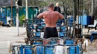 Seorang pria bersiap untuk berlatih mengangkat beban di outdoor gym atau pusat kebugaran terbuka di tepi Sungai Dnipro, Kiev, Ukraina, Kamis (18/4). Pusat kebugaran ini dibangun karena minimnya fasilitas olahraga yang terjangkau oleh warga. (AP Photo/Efrem Lukatsky)