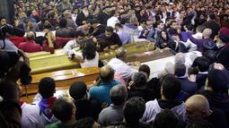 Umat Kristen Mesir memberikan penghormatan terakhir di samping peti jenazah korban serangan bom di Gereja Koptik St. George, Kota Tanta, utara Kairo, Minggu (9/4). Sebanyak 44 orang tewas dalam serangan bom di dua gereja koptik Mesir. (STRINGER/AFP)