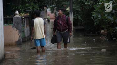 Warga beraktivitas saat banjir merendam kawasan Cipinang Melayu, Jakarta Timur, Senin (5/2). Akibat intensitas hujan yang cukup tinggi, permukiman di wilayah Cipinang Melayu tergenang air setinggi 30-40 cm. (Liputan6.com/Arya Manggala)
