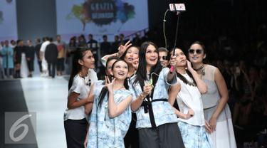 Artis sekaligus Desainer Luna Maya berselfie bersama para artis saat membawakan busana bertema midnight bloom di Jakarta Fashion Week (JFW) 2016, Senayan city, Jakarta (25/10/2015). (Liputan6.com/Herman Zakharia)