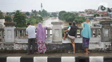 Sejumlah warga mengamati banjir yang menggenangi kawasan Rawajati dari atas flyover di Jakarta Timur, Rabu (1/1/2020). Banjir yang berasal dari luapan Sungai Ciliwung itu menjadi daya tarik tersendiri bagi sebagian pemotor yang melintasi di flyover tersebut. (Liputan6.com/Immanuel Antonius)