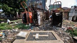 Sebuah makam berada dekat dengan gerobak sampah di TPU Menteng Pulo 2, Jakarta, Senin (9/12/2019). Minimnya kesadaran warga setempat ditambah tidak adanya fasilitas TPA dan perawatan pengelola TPU menyebabkan kondisi kompleks makam memprihatinkan akibat dipenuhi sampah.(merdeka.com/Iqbal S. Nugroho)
