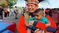 Kepala BNPB Doni Monardo sedang menggendong 'Doni Monardo' kecil saat acara Kebersamaan dalam se-Helai Papeda di Bumi Kenambai Umbai, Sentani, Jayapura, Selasa (3/9/2019). (Dok Badan Nasional Penanggulangan Bencana/BNPB)