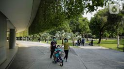Warga mendampingi anaknya bermain sepeda di Lapangan Banteng, Jakarta, Sabtu (23/10/2021). Pembukaan 59 RTH ini menyusul penurunan status Pemberlakuan Pembatasan Kegiatan Masyarakat atau PPKM Jakarta yang kini berada di level dua. (Liputan6.com/Faizal Fanani)