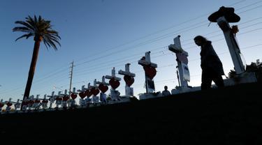 Manuela Barela melintas dekat deretan nisan yang disiapkan untuk menghormati korban tewas penembakan massal Las Vegas di Nevada, Jumat (6/10). Sebanyak 58 nisan kayu berbentuk salib itu ditambahkan ornamen bentuk hati berwarna merah. (AP/Gregory Bull)